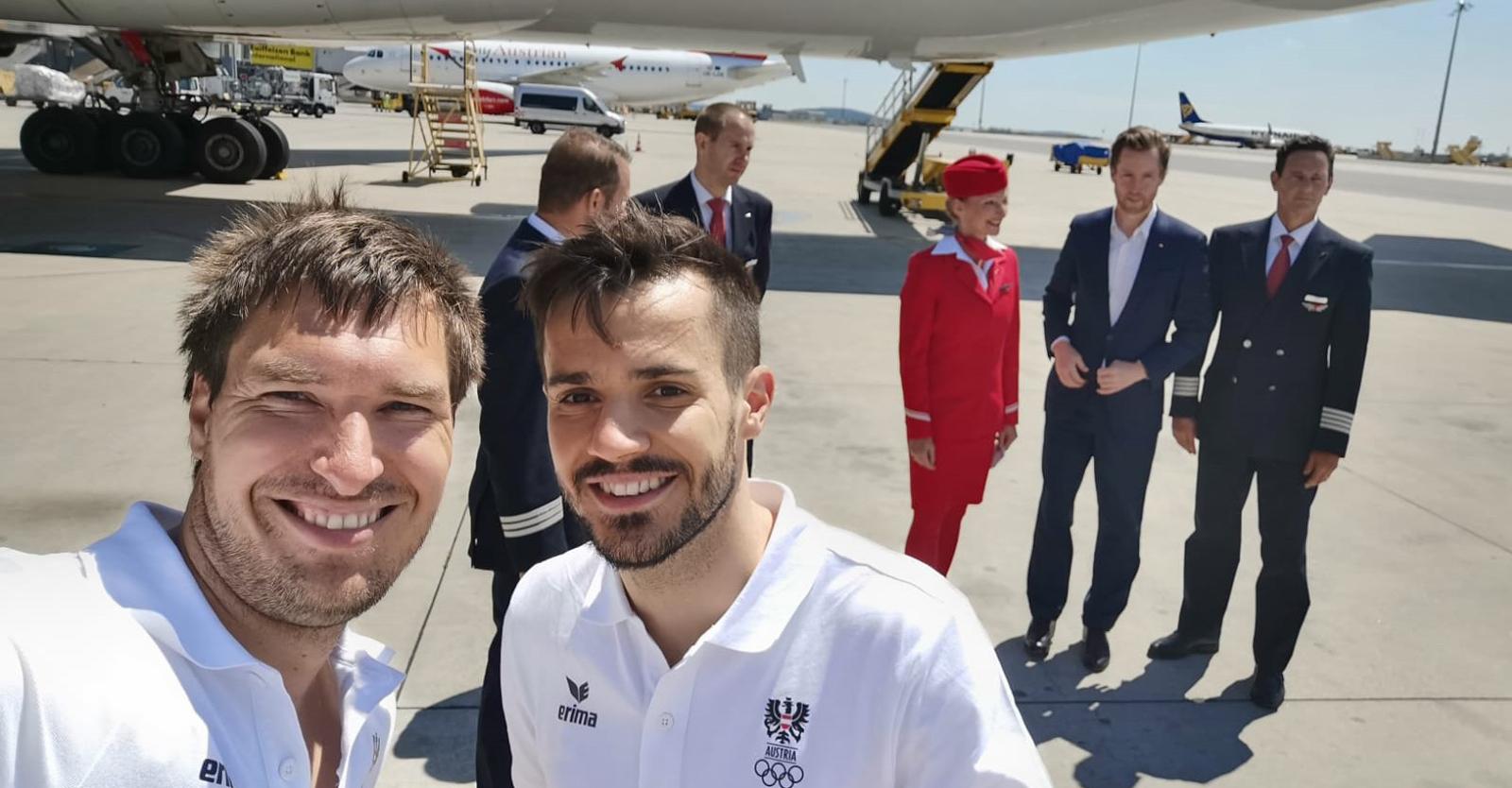 Martin Strempfl mit Badmintonspieler Luka Wraber vor der Austrian-Airlines-Maschine und Crew